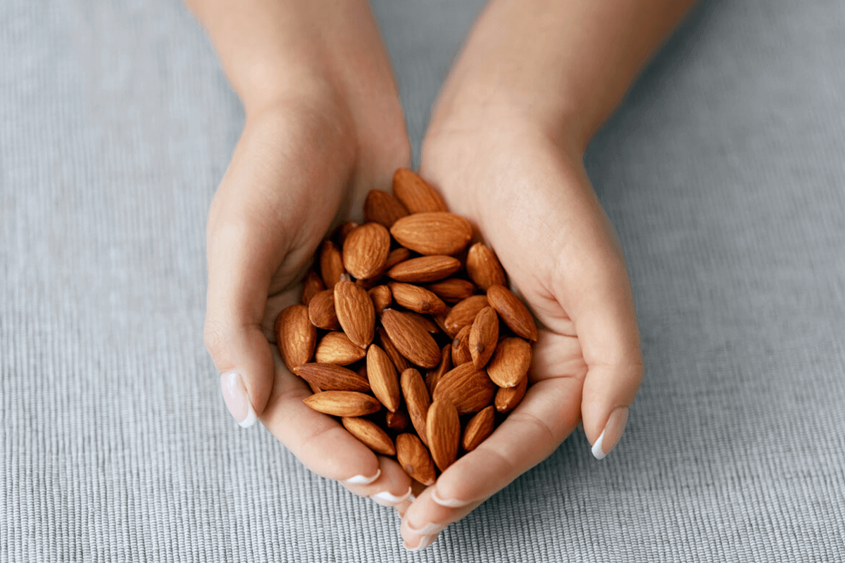 close up of hands holding almonds