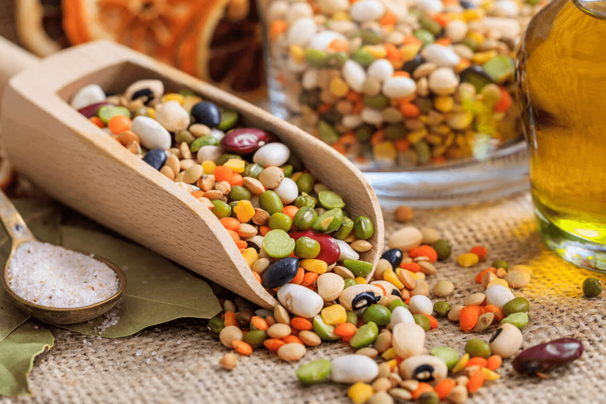 mixed raw legumes pulses on wooden spoon