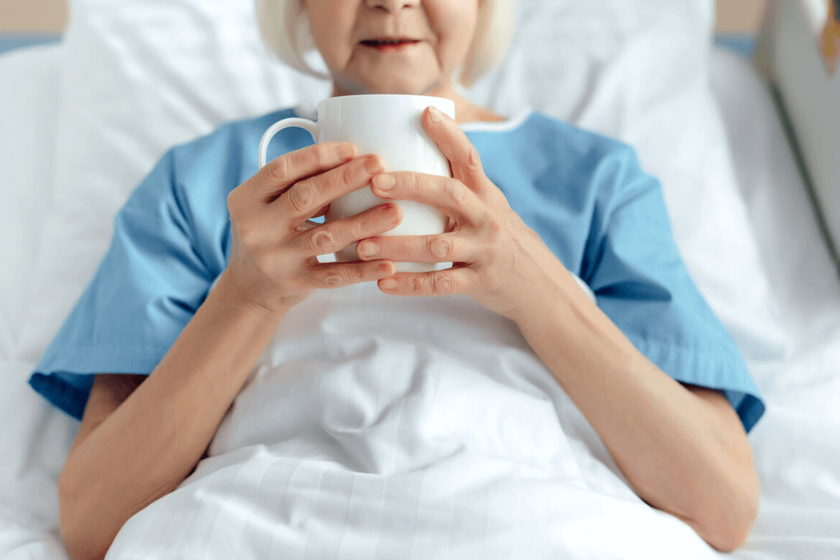 woman laying in hospital bed drinking tea from a white mug