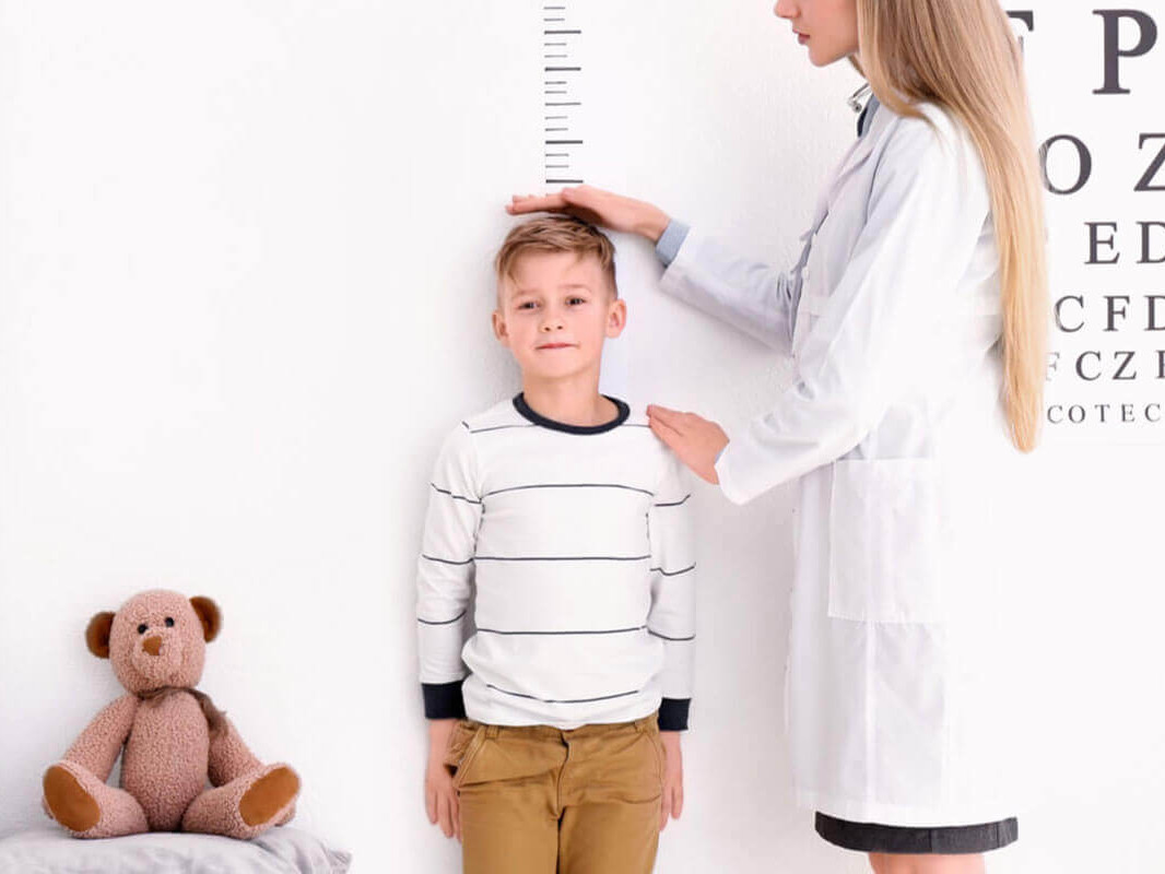 optometrist measuring the height of a boy