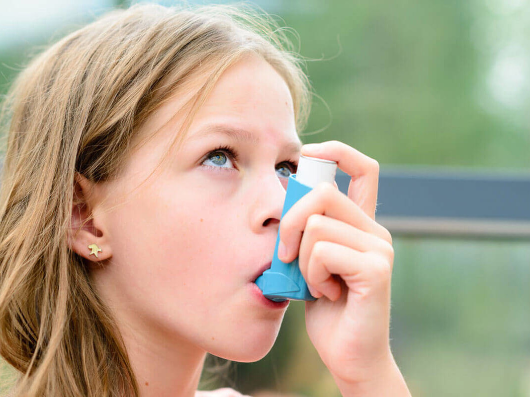 Young girl using an inhaler for an asthma attack