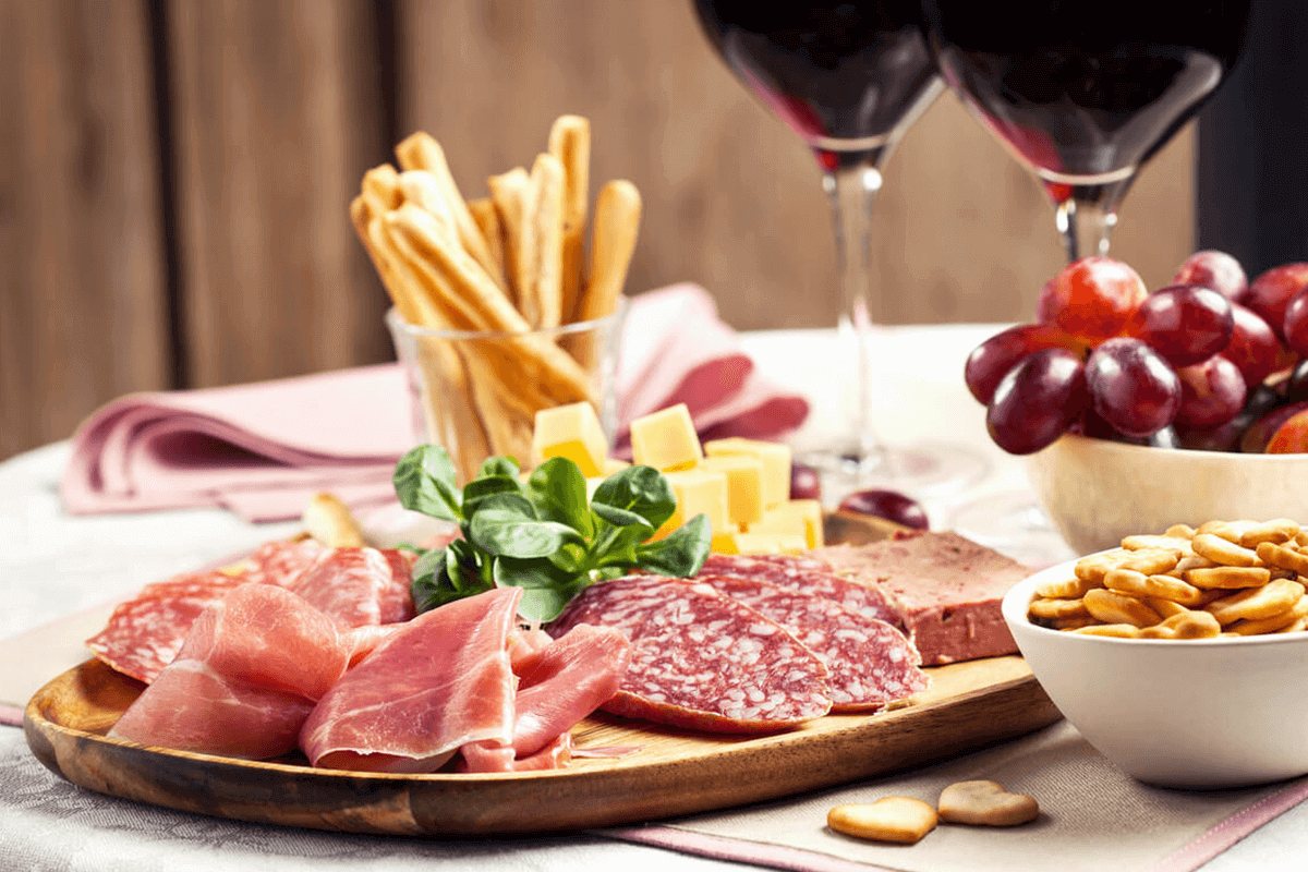Wine, meat, and cheese snack board.