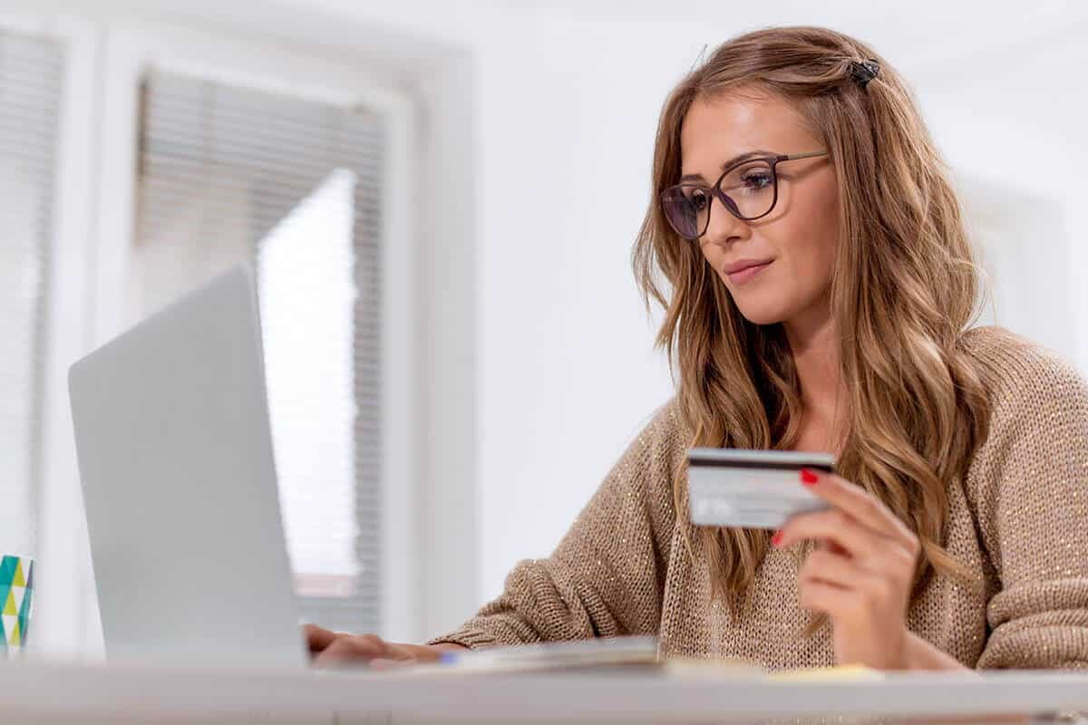 woman at her laptop with credit card in her hand, ready to make a payment online