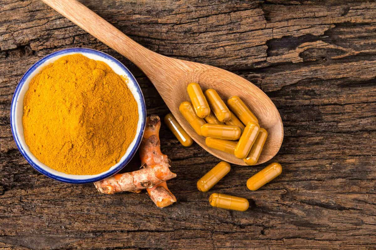 Turmeric root and turmeric powder rest on a wooden surface next to curcumin supplement capsules on a wooden spoon.