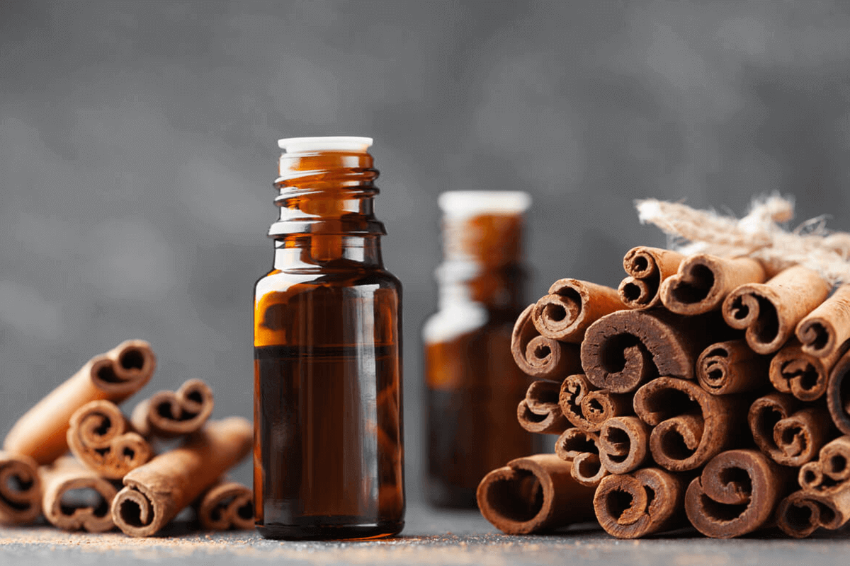 cinnamon sticks and cinnamon essential oil in a bottle