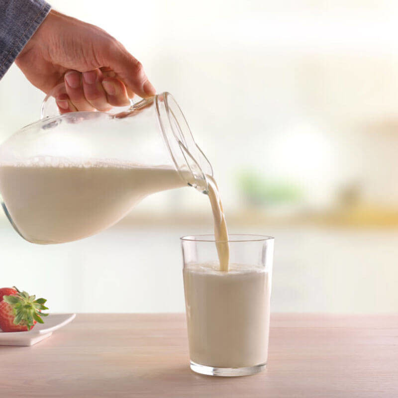 person pouring milk from jug into glass