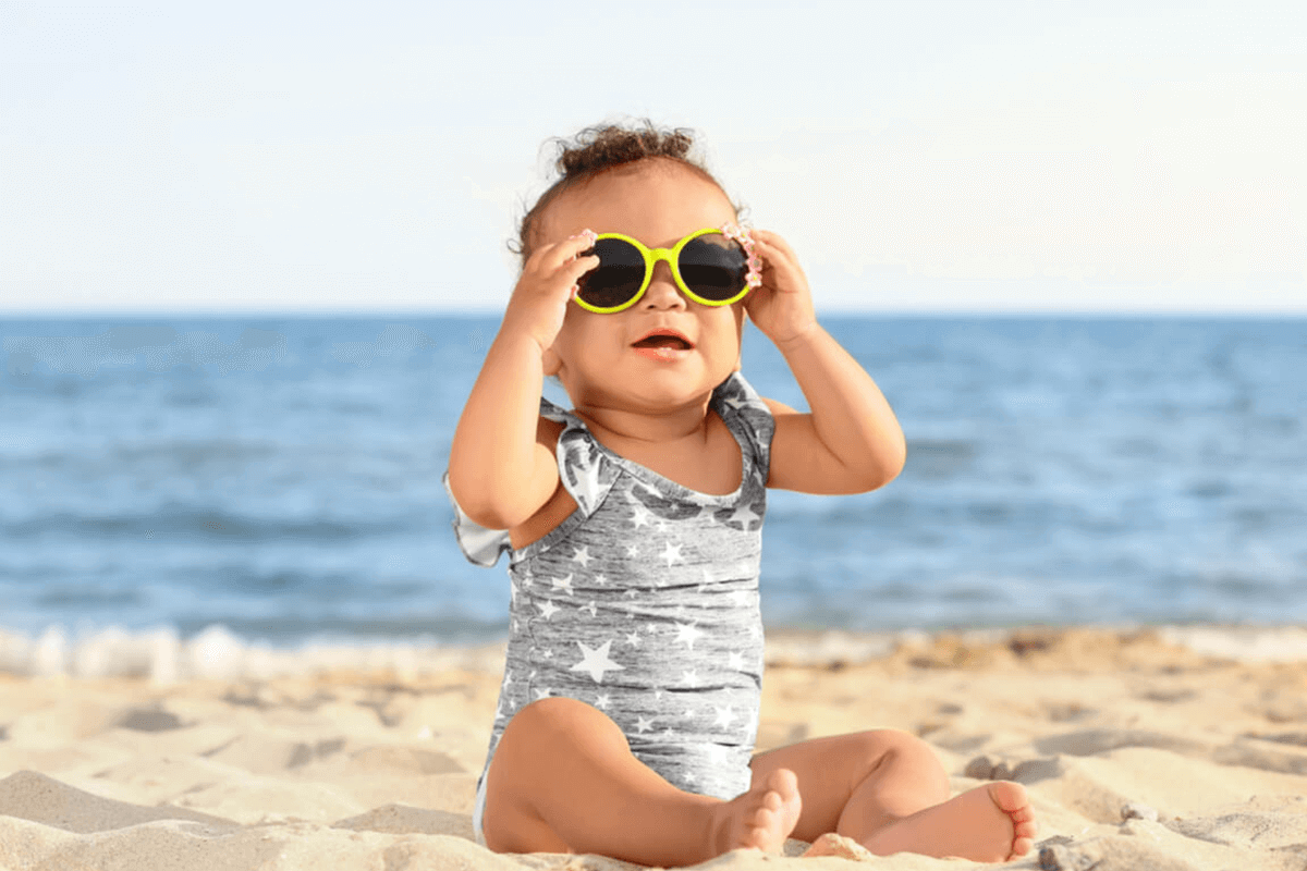 child sitting outdoors on a beach with sunglasses on