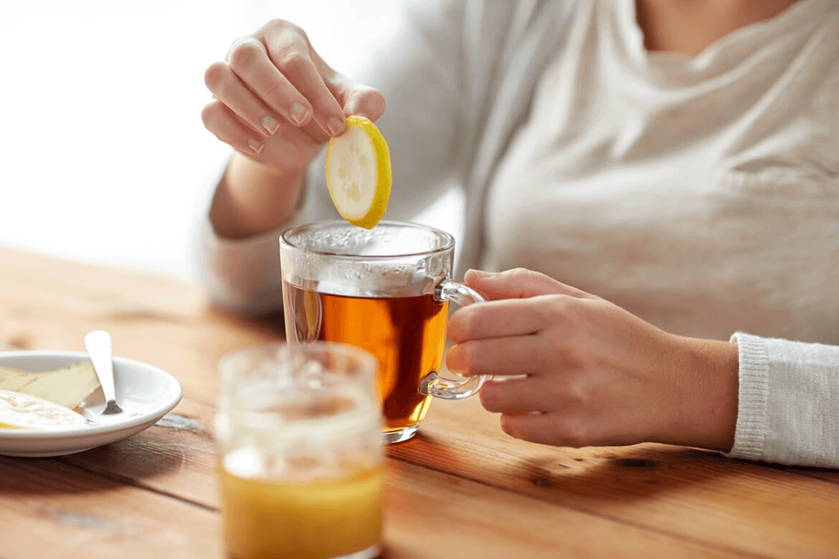 person adding ginger to tea