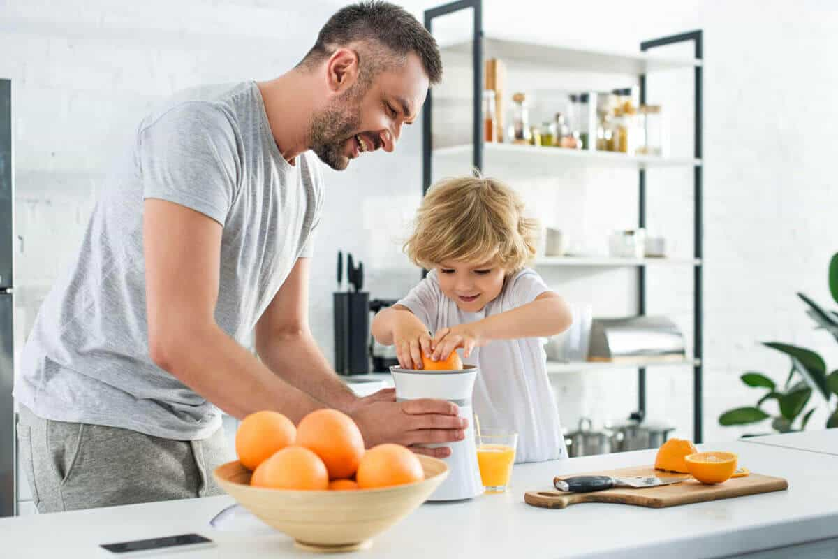 father and daughter making fresh orange juice in kitchen