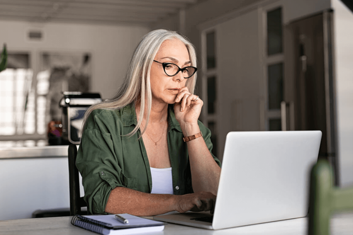 woman looking at her laptop and thinking