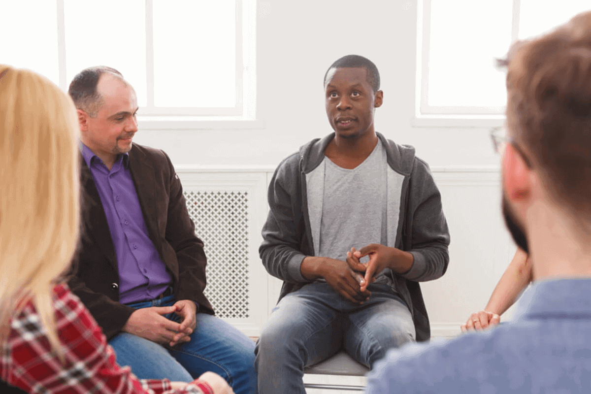 Young man speaking during group therapy in a bright room