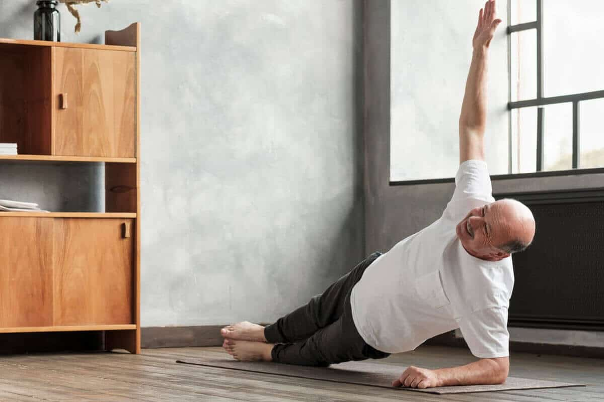 older man in a side plank pose in living room