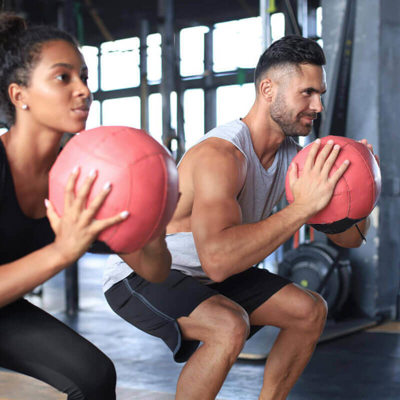 man and woman squatting in the gym with exercise balls
