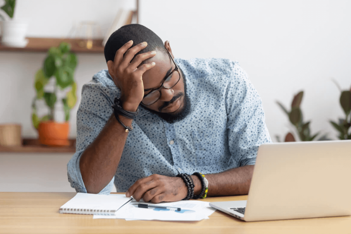 man holding his head looking at computer feeling tired