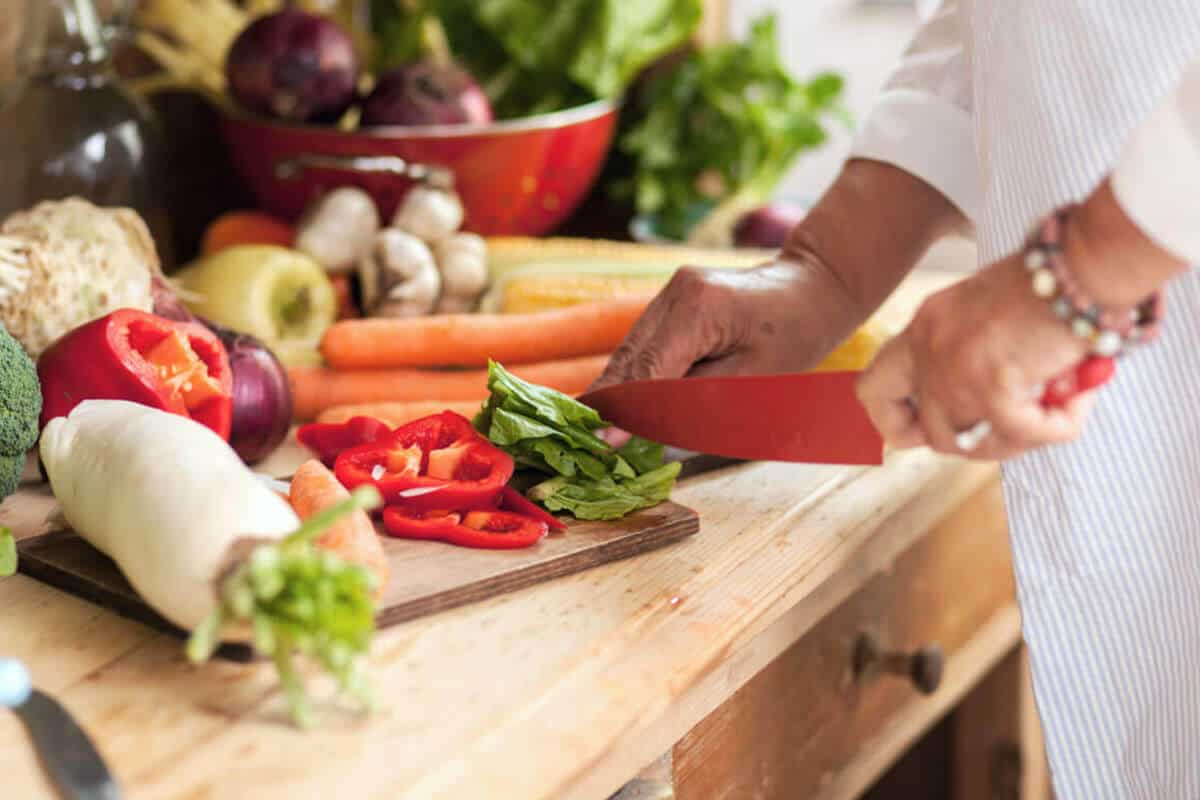 person cutting up vegetables on a wooden board in kitchen