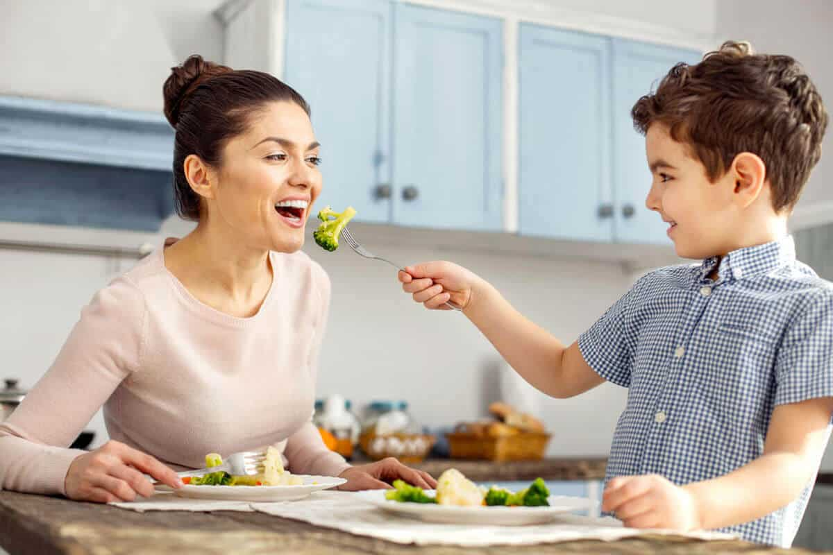 child feeding his mother a piece of broccoli