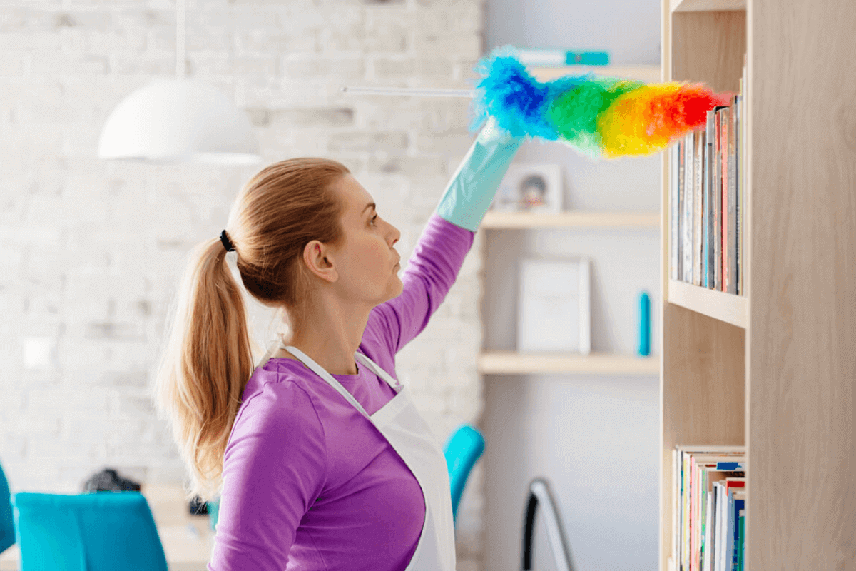 Woman cleaning high shelf with duster