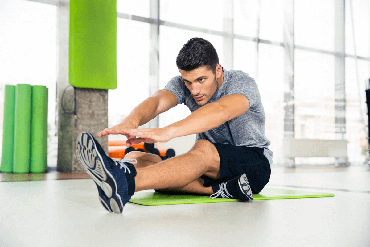 man sitting and stretching his arms and legs