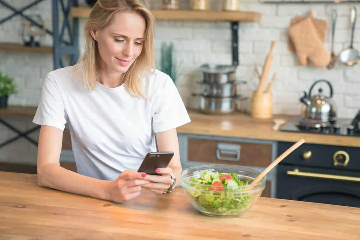 woman on her phone about to eat a salad