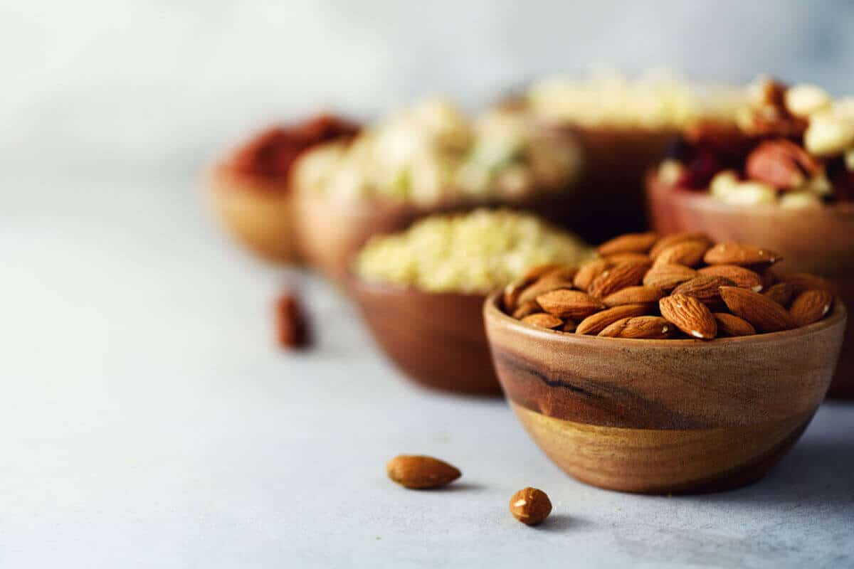 Almonds and mixed nuts in wooden bowls on a light counter