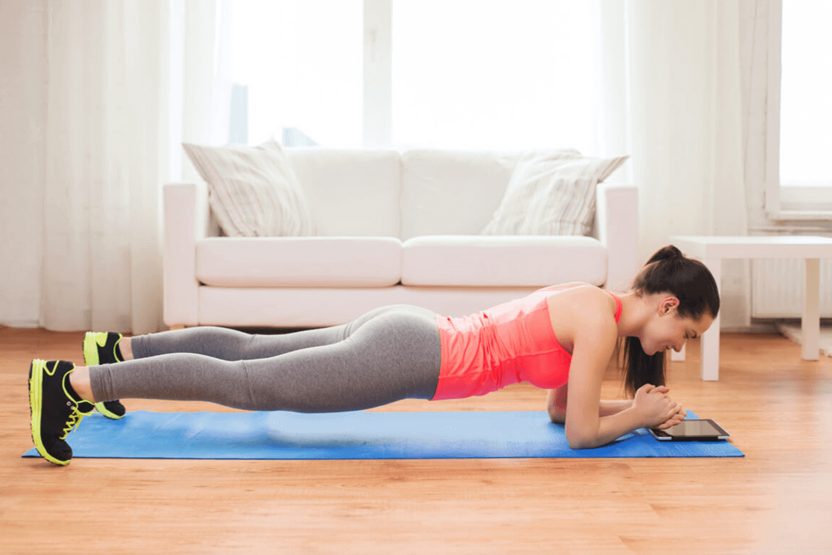 Strong young woman doing core workout on a mat in a gym