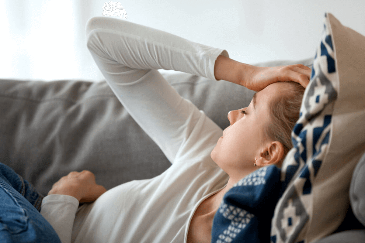 woman on couch laying down and holding head