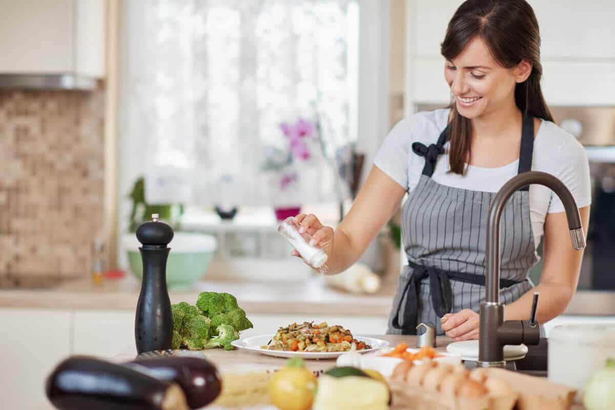 woman putting salt on her meal in kitchen
