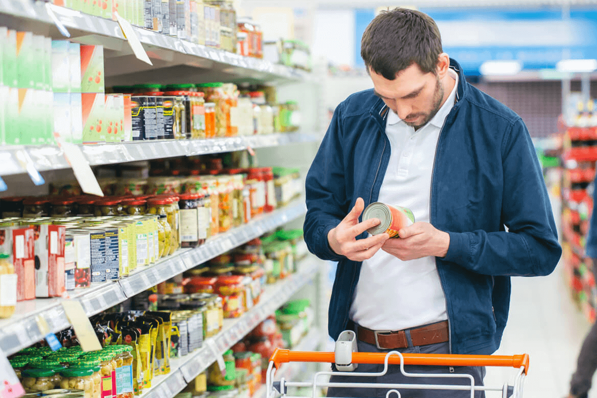 man reading the label of a food can