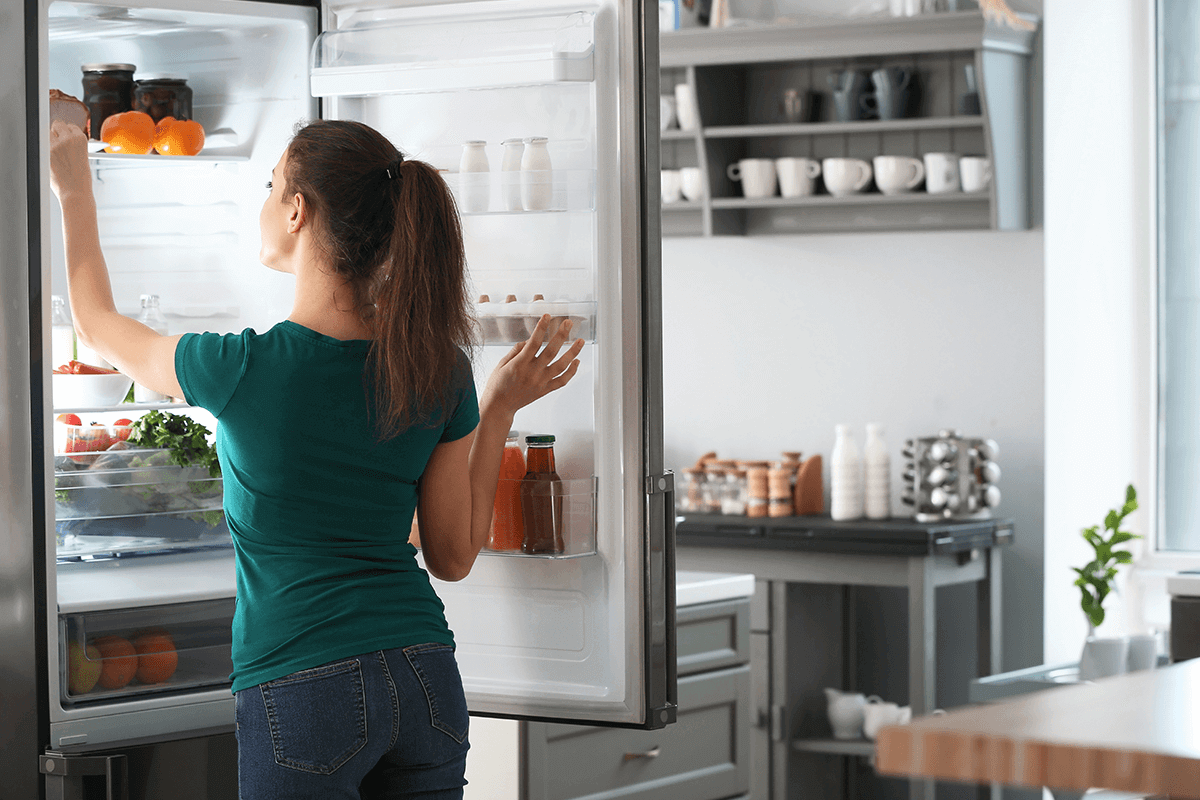 woman putting something into her fridge