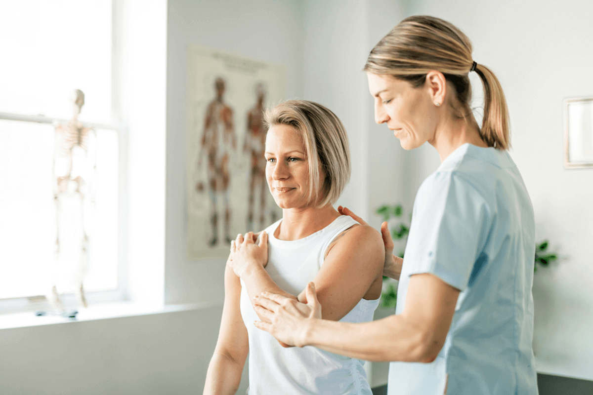 healthcare practitioner helping patient move their arm for mobility improvement