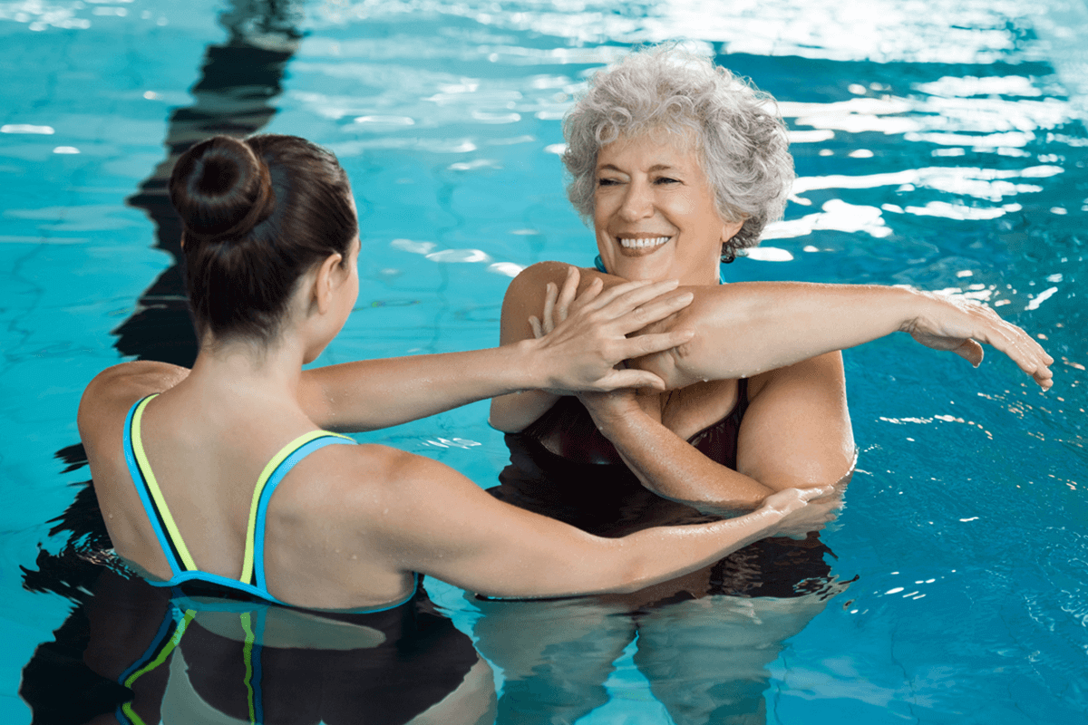 trainer with woman in the pool guiding in aquatic exercise