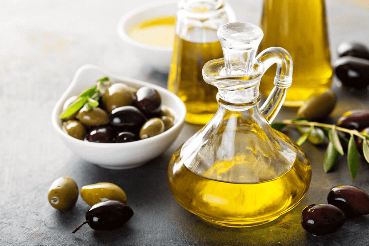 Olive oil in glasses and olives in a white dish next to the oil