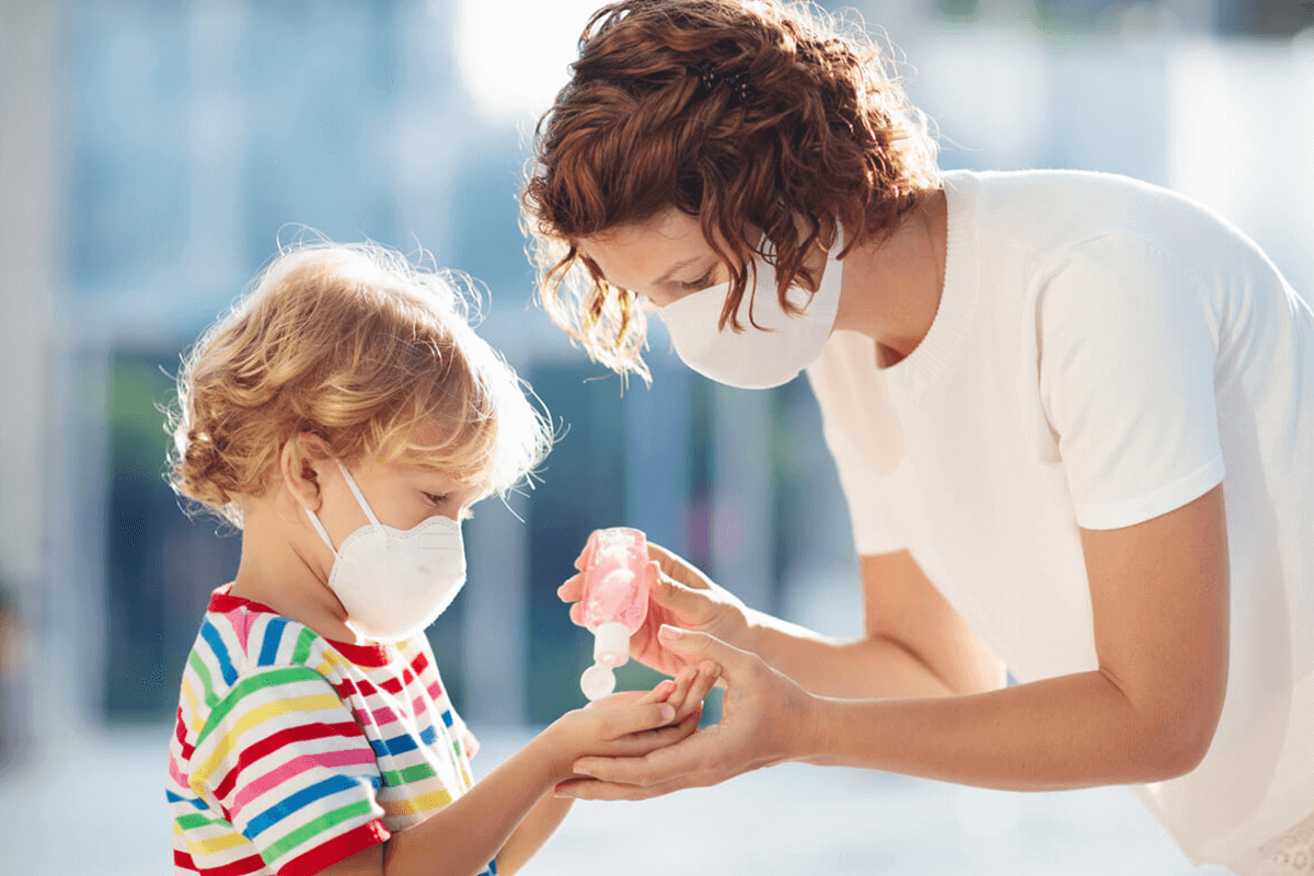 woman and child with face masks applying hand sanitizer to their hands