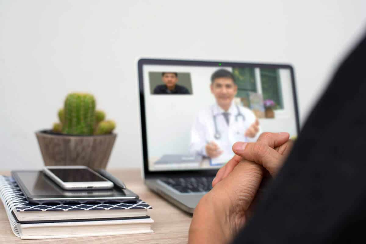 practitioner on a laptop screen talking to their patient