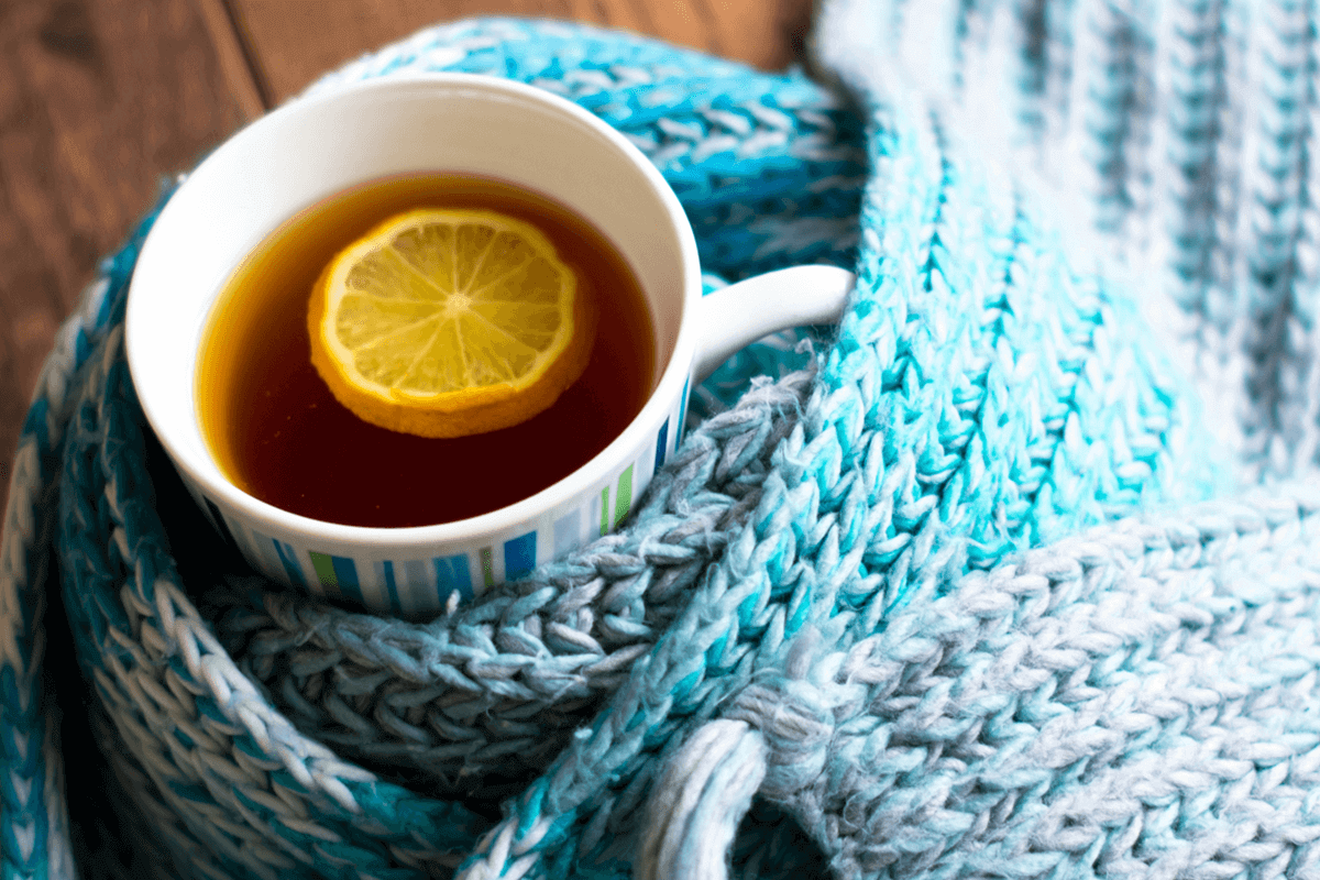 hot tea with a lemon slice in it wrapped by a scarf