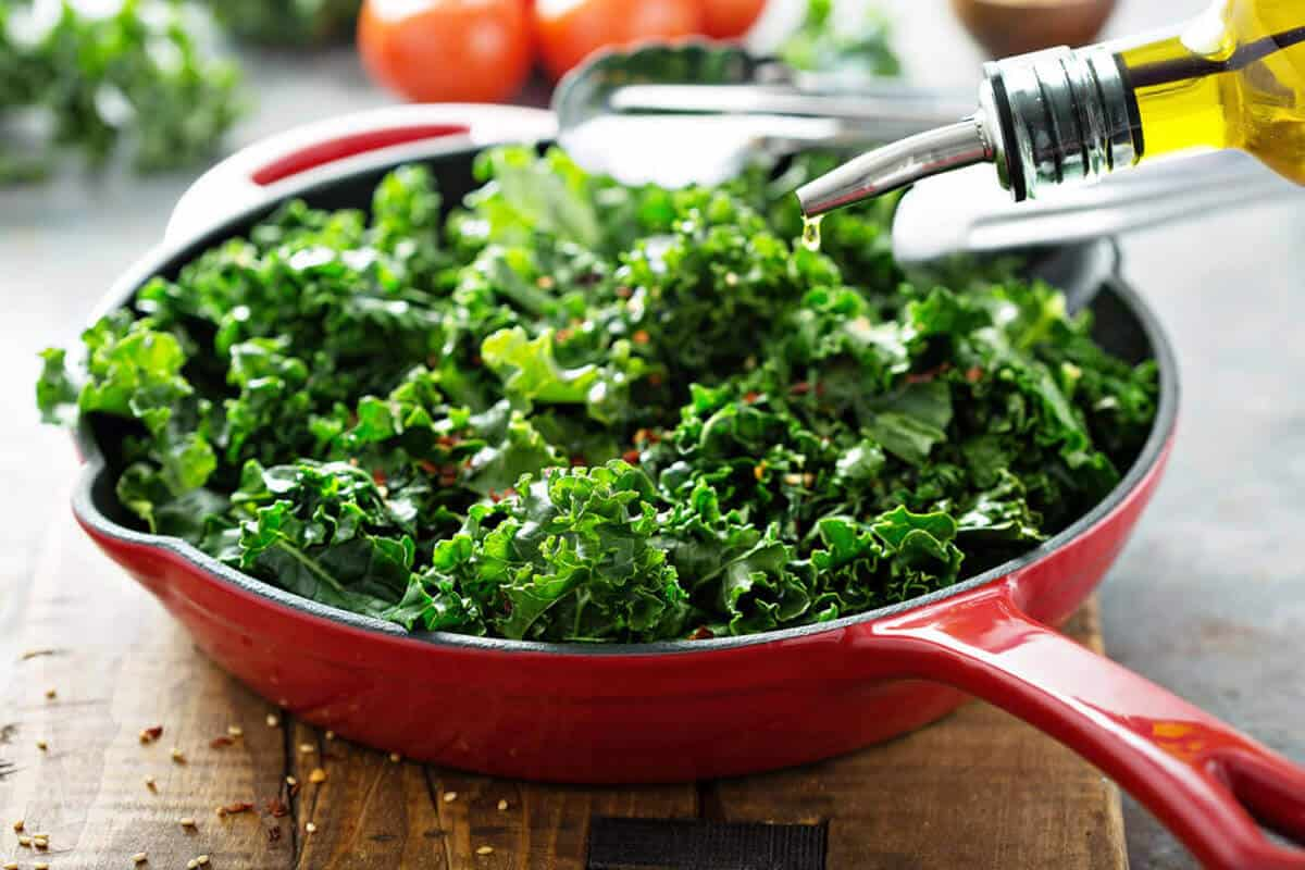 kale in a pan with oil being sprinkled on it