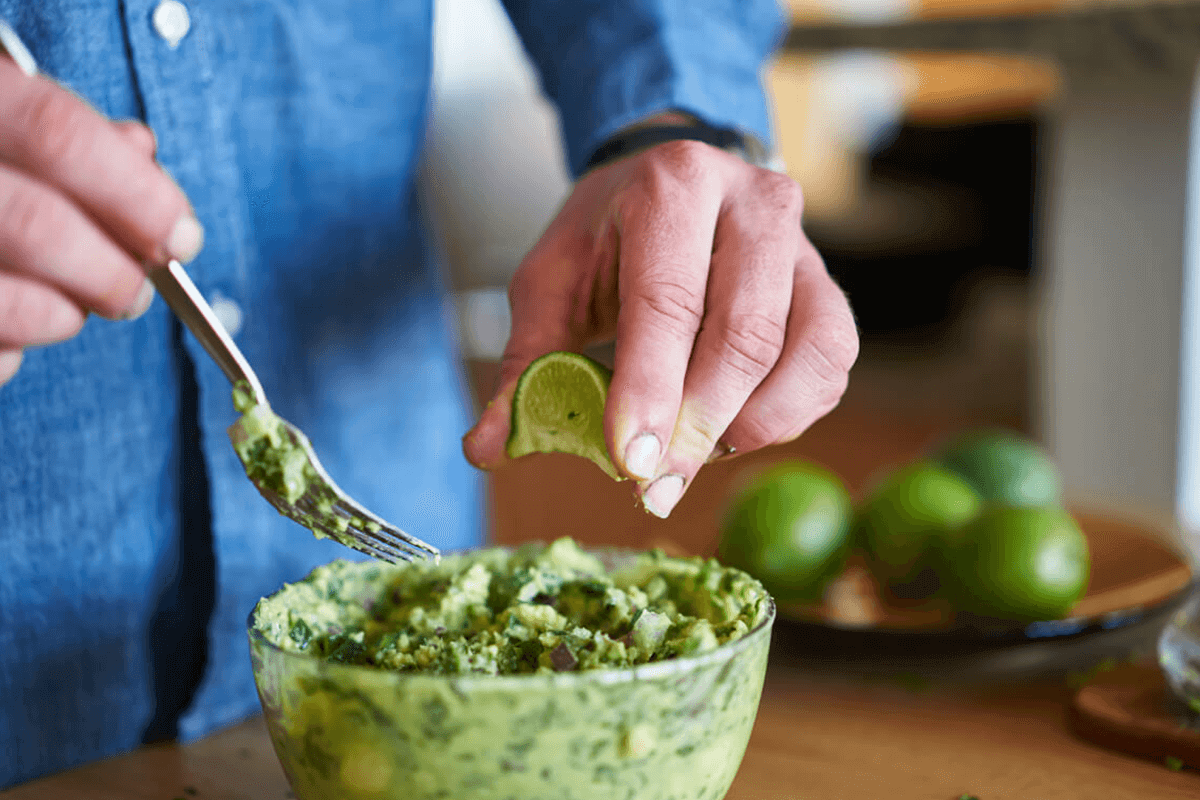 man making guacamole with french avocados and lime