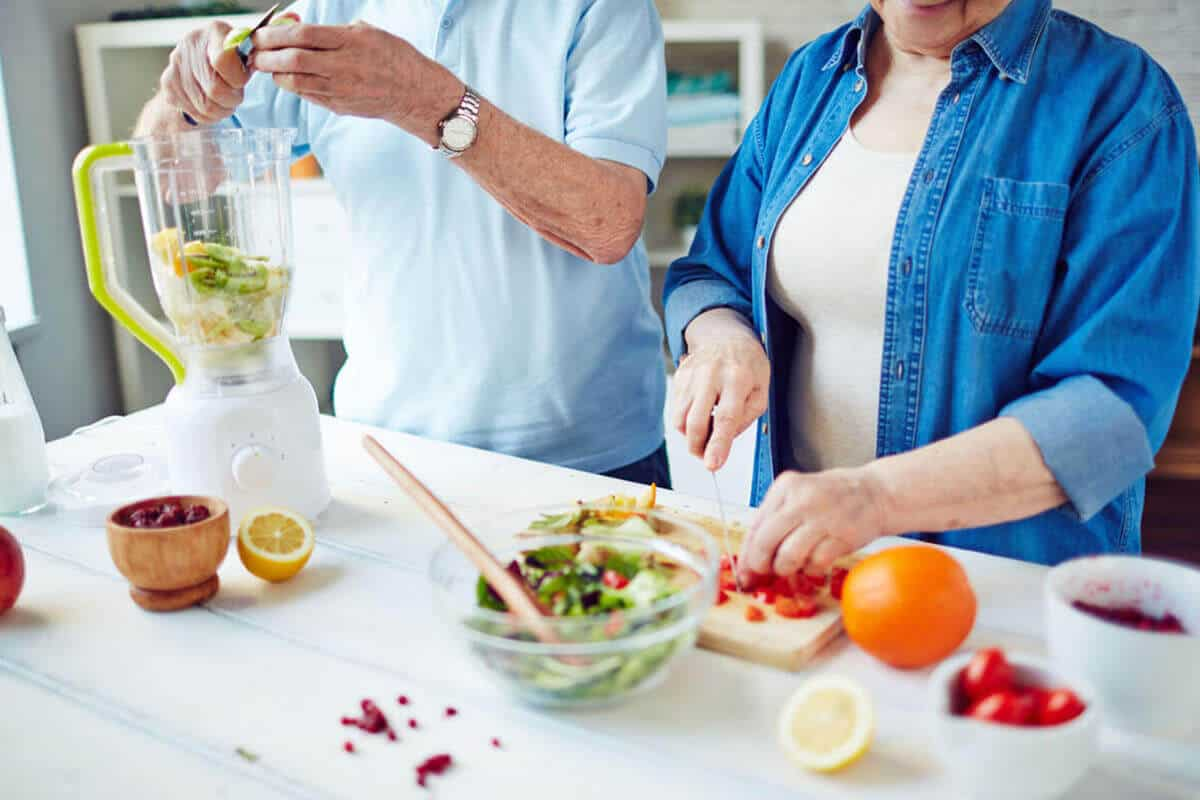 Elderly couple making healthy smoothie in kitchen