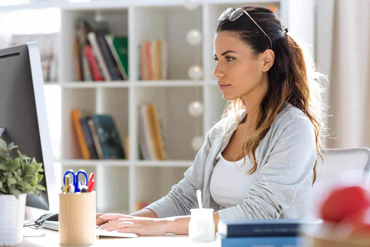 woman on her laptop focused with yogurt next to her