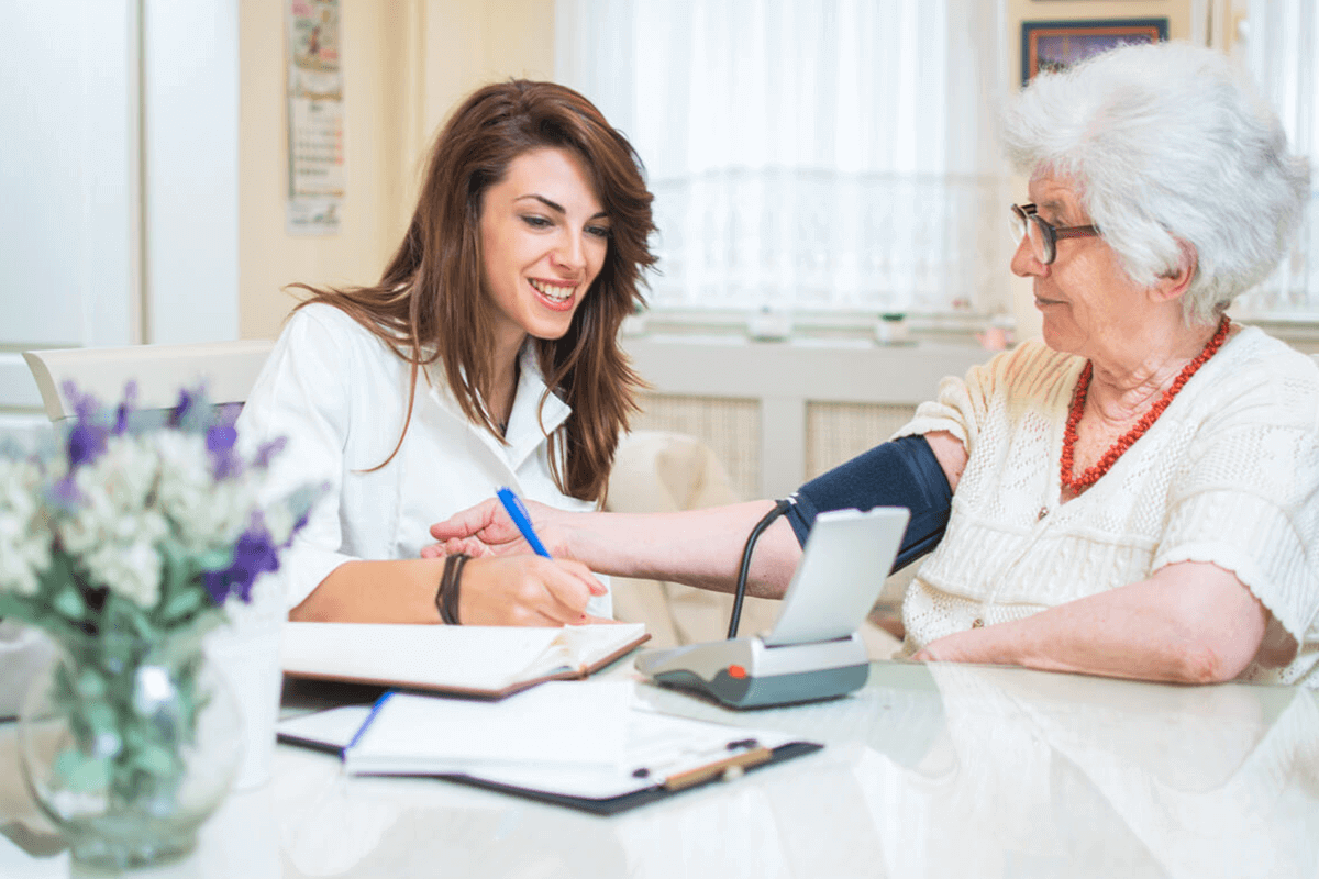 nurse taking an elderly woman's blood pressure