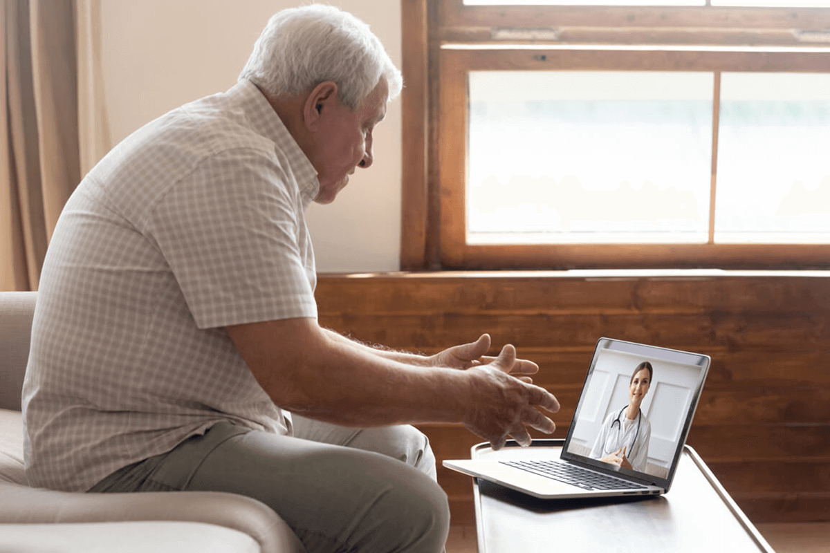 older man talking to healthcare practitioners on video chat through his computer, at home