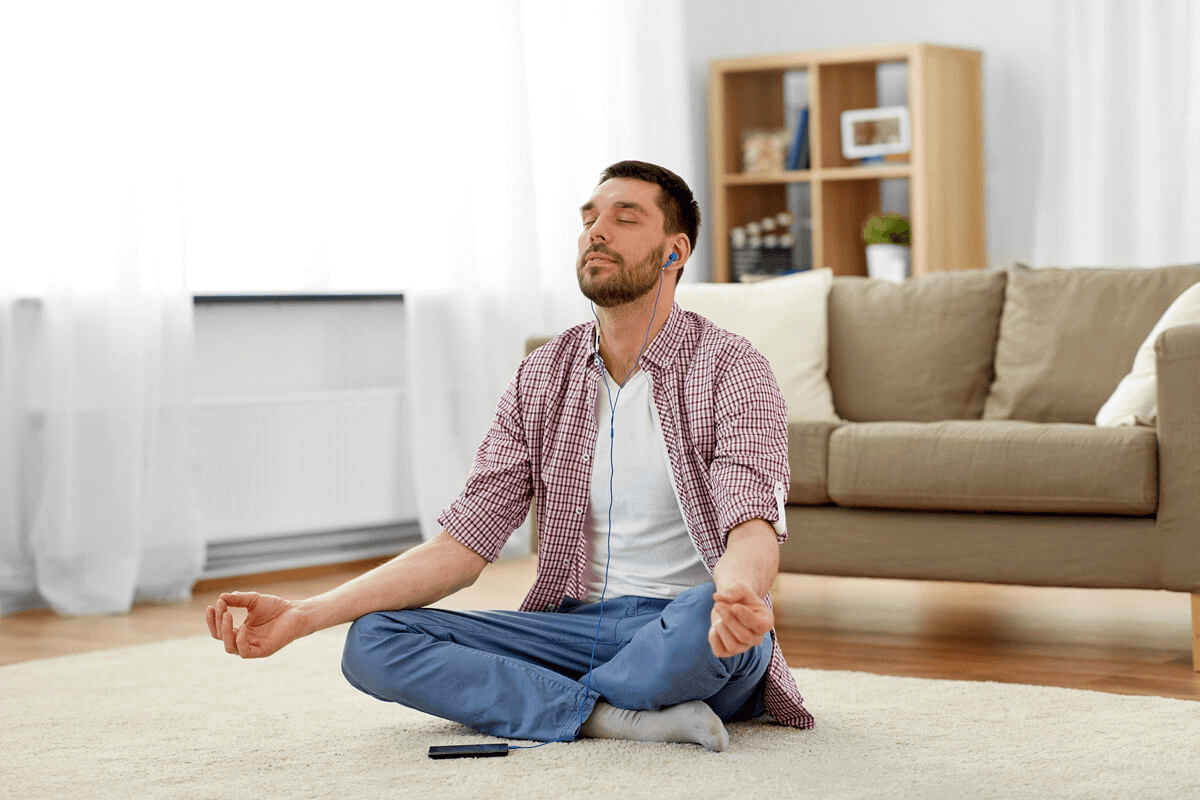 man sitting in his home meditating with headphones