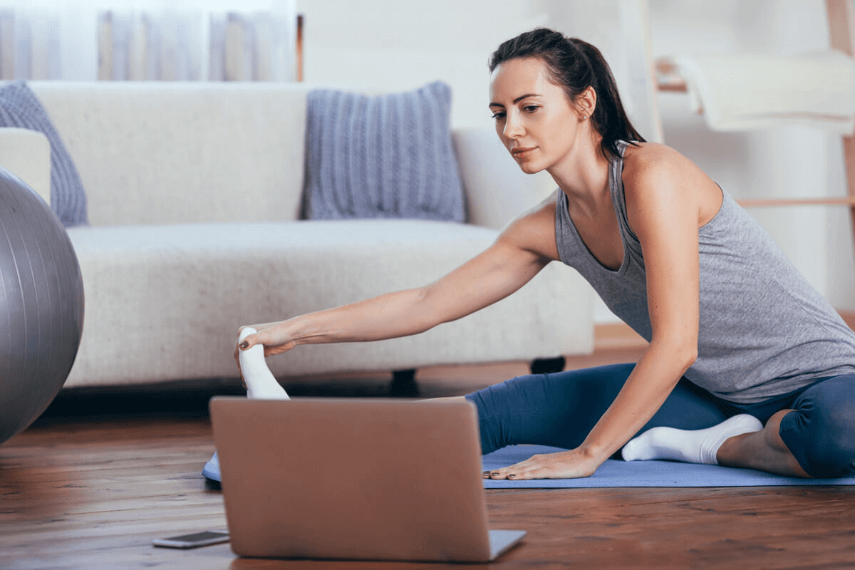 woman looking at her laptop in her living room stretching before a workout