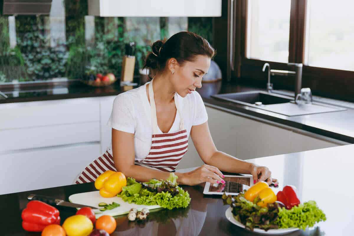 woman with vegetables in kitchen looking at an iPad before cooking