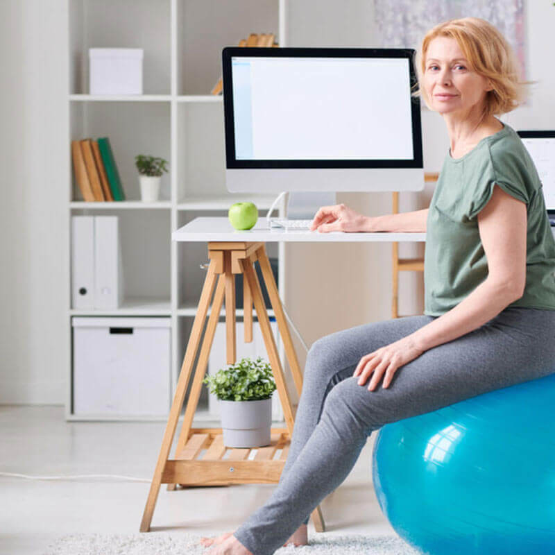woman sitting on a gym ball at her desk set up at home