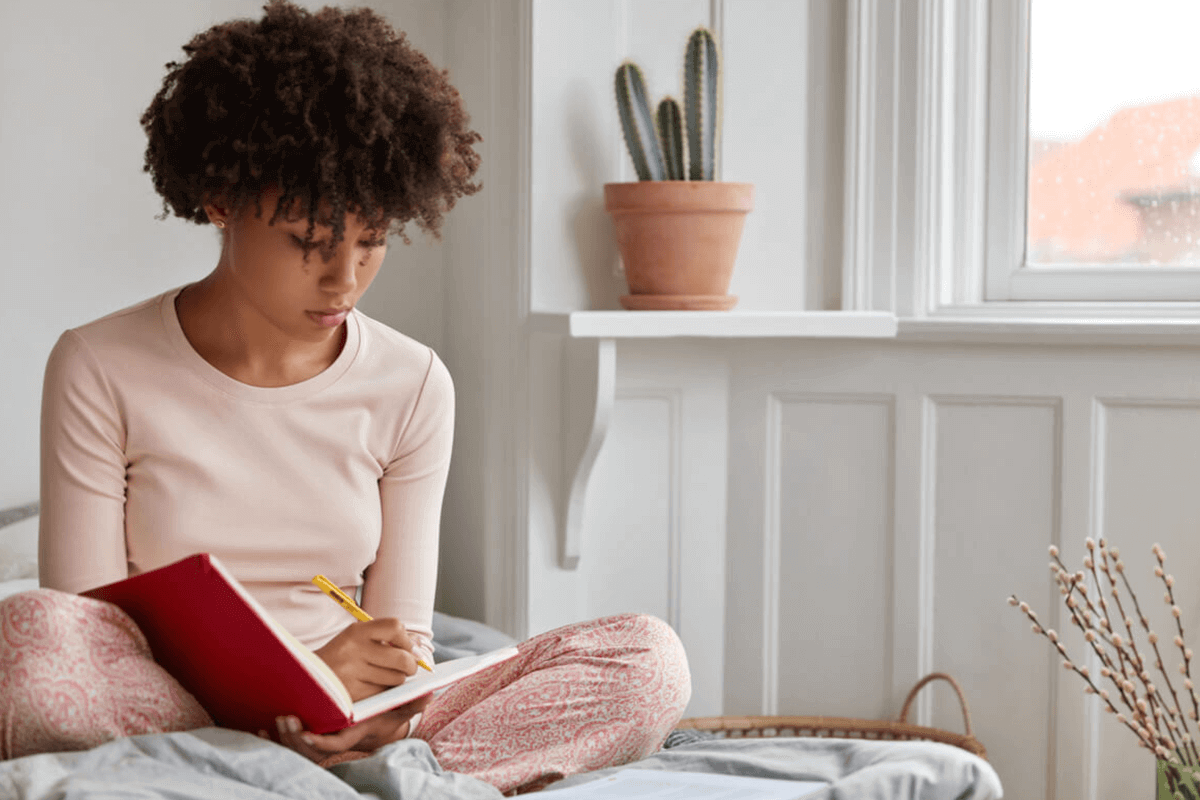 woman sitting on her bed writing in a journal