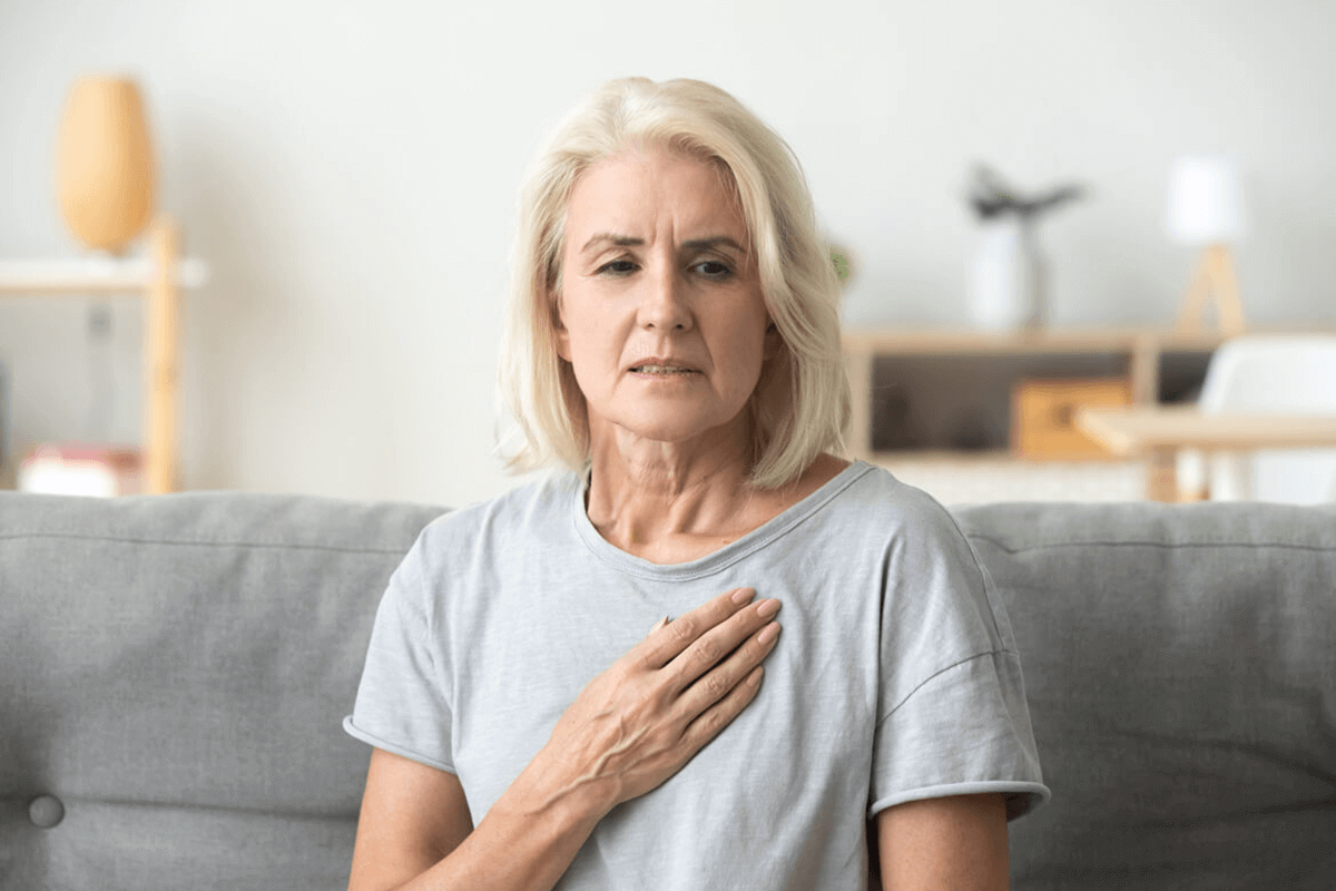 woman sitting on couch holding her chest
