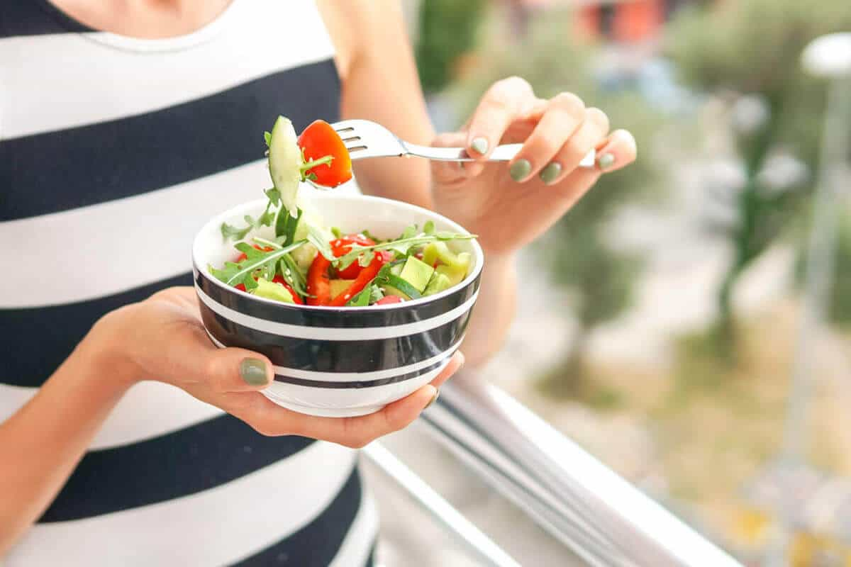 close up of bowl with raw vegetables in salad form and a woman holding a fork, eating the salad