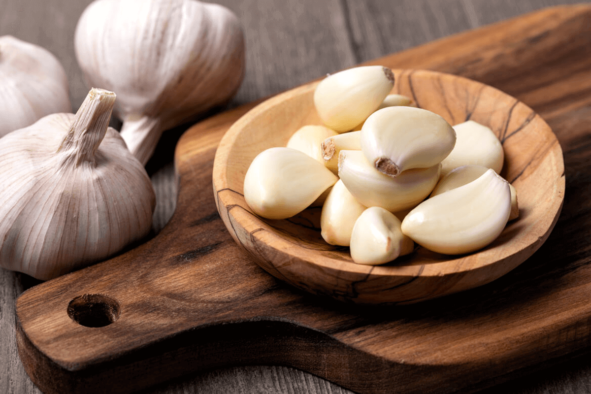 garlic gloves in a wooden bowl on a wooden cutting board with raw garlic next to it