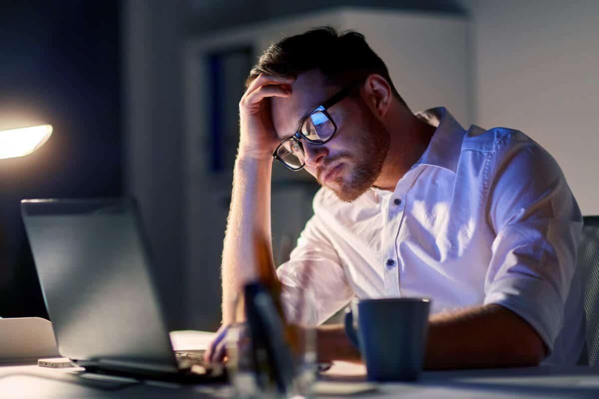 man looking at his laptop at night